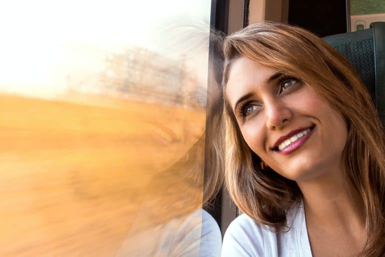 Smiling woman dreamily looking out a window