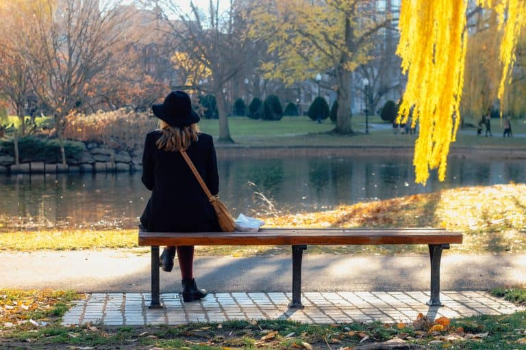 Lady siting on a park bench gazing at a pond