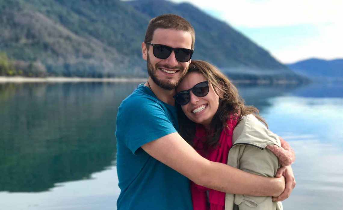 Smiling couple in front of peaceful lake and mountain. Man has his arms around wife in a sweet embrace.