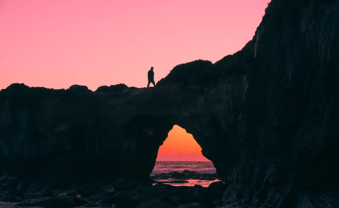 Man walking on rock outcrop with sunset in the background